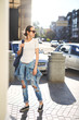 Model wearing plain white t-shirt, boyfriend jeans, sneakers and hipster sunglasses posing against street, teen urban clothing style.