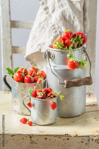 Delicious and fresh wild strawberries in the old metal mug