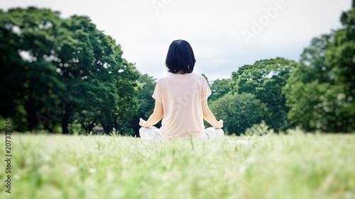 Photo 自然あふれる芝生の上で瞑想をする女性