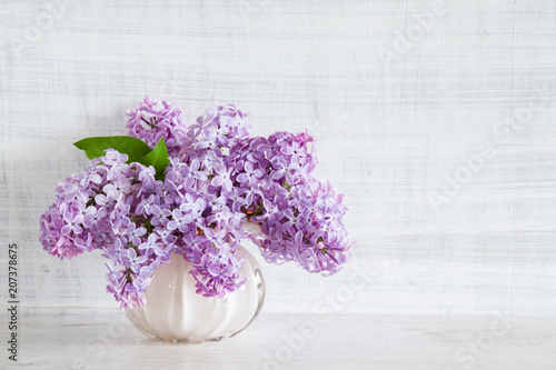 In de dag Lilac Fresh branches of purple lilac blossoms in vase on wooden table. Vintage greeting card. Mockup for positive ideas. Empty place for inspirational, emotional, sentimental text or quote. Front view.