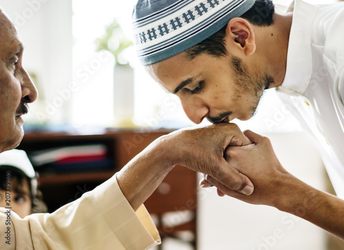 Vászonkép Young Muslim man showing respect to his father