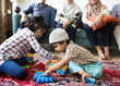 Leinwanddruck Bild - Muslim family relaxing and playing at home