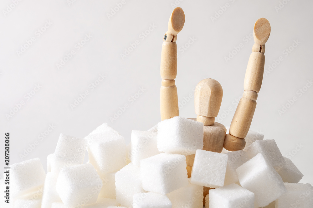 Fototapeta Sugar addiction, insulin resistance, unhealthy diet and November 14 is diabetes awareness day concept with a puppet drowning in sugar cubes isolated on white background and copy space for text