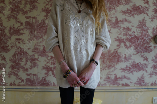 Photo Young woman with thin hands, standing on bed in bedroom, alone