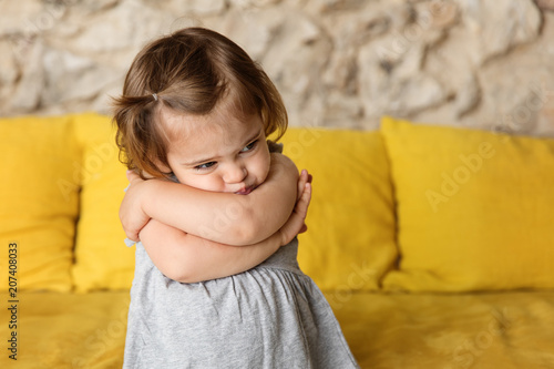 Pouting little girl with crossed arms on yellow couch