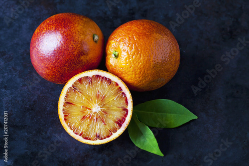 Two whole and a half blood orange on dark ground