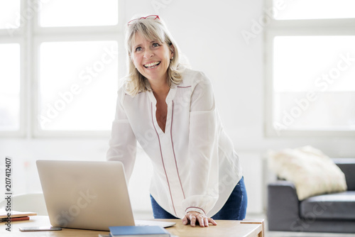 Portrait of happy mature businesswoman with laptop leaning on desk