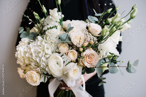 Young florist woman holding freshly made blossoming flower bouquet in white colours of hydrangea, roses, ranunculus, eustoma, carnations, eucalyptus on the grey wall background. © anastasianess