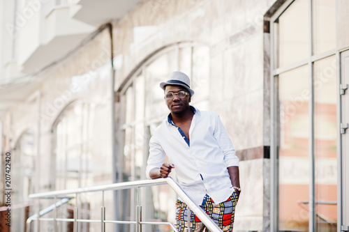 05ee757a28af Stylish african american man in white shirt and colored pants with hat and  glasses posed outdoor