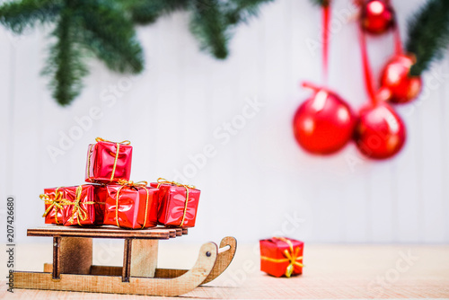 Christmas Gift Boxes And Xmas Sleigh On Wooden Table Over Blurred