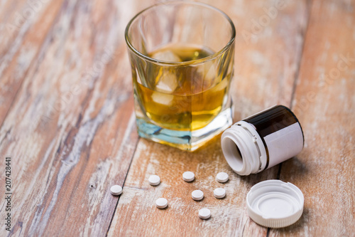 Fotobehang Bar drug abuse, addiction and suicide concept - glass of alcohol and pills on table