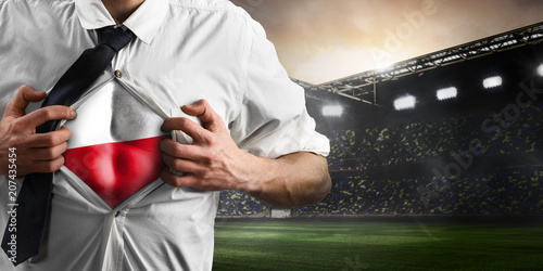 Poland soccer or football supporter showing flag under his business shirt on stadium.