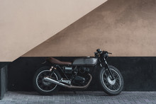 A Vintage Motorcycle Leaning Against A Wall