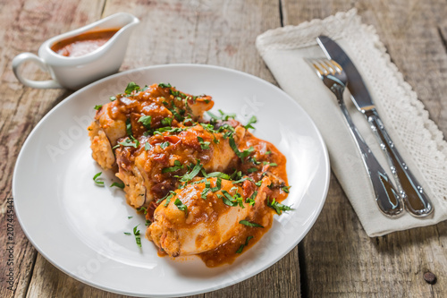 Fototapeta Squid stuffed with rice, olives and feta cheese in tomato sauce obraz
