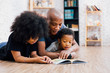 Leinwandbild Motiv African American father reading a fairy tale fable story for kids at home. Happy family lying on the floor indoors