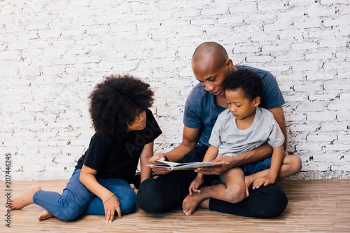 Fényképezés African American father reading a fairy tale fable story for kids at home
