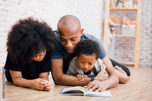 African American father reading a fairy tale fable story for kids at home Canvas-taulu