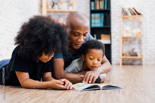 Valokuva  African American father reading a fairy tale fable story for kids at home