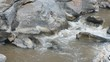 panning of the water fast flowing in the rocky stream
