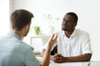 canvas print picture - African American employer listening attentively to caucasian job applicant talking at work interview, being friendly and interested to candidate. Concept of recruiting, employment, hiring