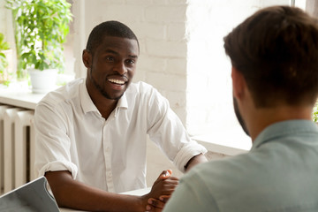 Smiling African American worker talking to colleague considering company work related issues, chatting on break, counseling, discussing latest news. Coworkers having casual conversation at workplace