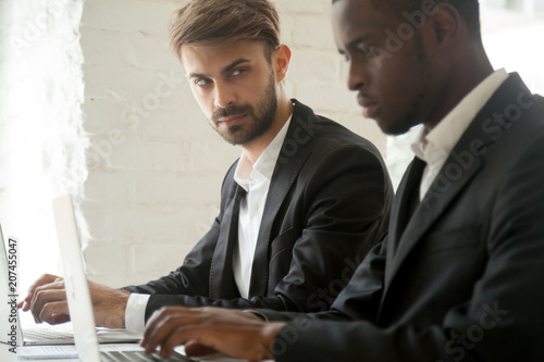 Fotografia Suspicious cunning male Caucasian worker looking at serious working African American colleague, feeling mad and sneaky distrusting, having doubts, planning