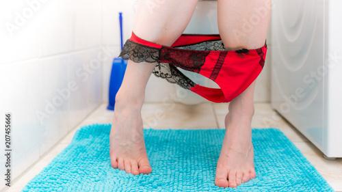 Junge Frau mit roten Tanga sitzt auf der Toilette - kaufen
