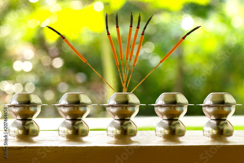Foto op Canvas Zen Burning orange incense joss stick on a holder with green background