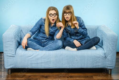 Two shocked women holding fake eyeglasses on stick Wallpaper Mural