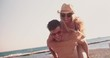 Young hipster couple on summer holidays enjoying piggy back ride