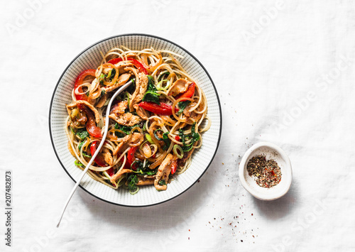 Photo Teriyaki chicken, bell peppers, onions, spinach and rice noodles stir fry on white background, top view