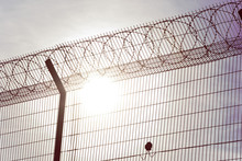 Fence With Barbed Wire On The Background Of The Sun