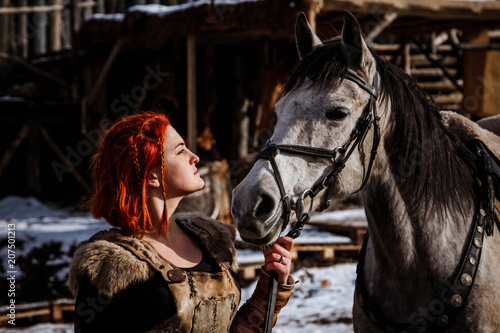 Fotografie, Obraz  Red-haired woman with a faithful horse preparing for battle