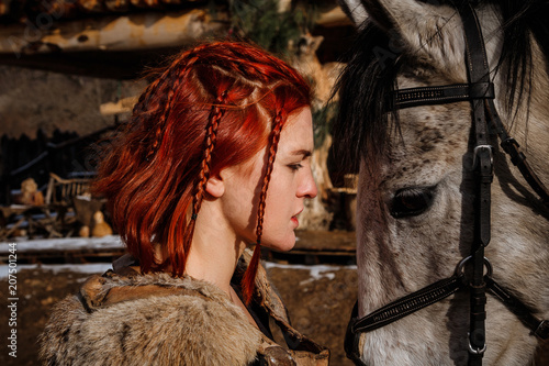 Photo  Red-haired woman with a faithful horse preparing for battle