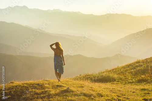 Canvas Prints Honey girl in dress standing on grass in sunset mountains