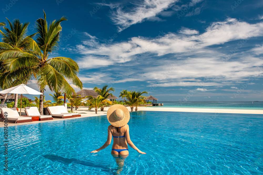Fototapeta Woman with hat at beach pool in Maldives