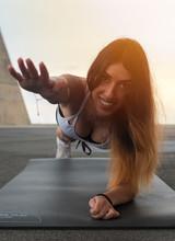 Chica Sonriendo Haciendo Plncha Con Atardecer De Fondo