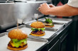 canvas print picture - Burger Restaurant. Closeup Chef Cooking Burgers In Kitchen.