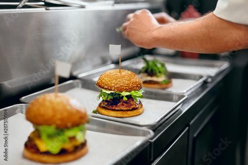 Fotobehang Restaurant Burger Restaurant. Closeup Chef Cooking Burgers In Kitchen.