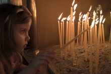 Little Girl Prays And Puts A Candle In Orthodox Church