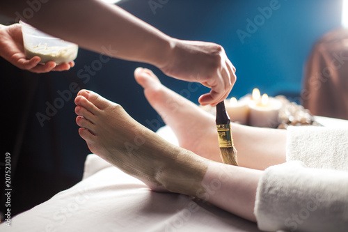 Valokuva  Close up of spa worker female hands aplying mad clay mask on female client foot in salon