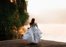 The Fairy Near Water.  Girl In White Dress On Lake. Woman On A Wooden Bridge. Fantastic Big Lake. Mysterious Foggy Forest. Fashion Toning. Creative Color