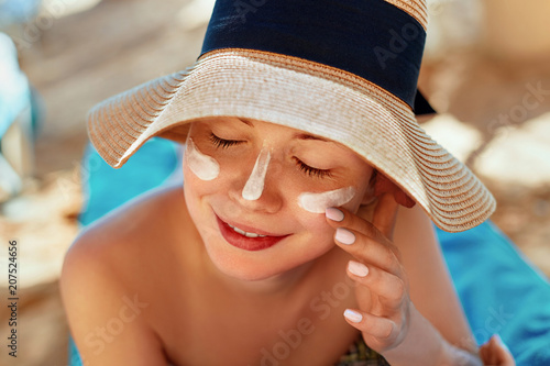 Facial Care. Female Applying Sun Cream and Smiling. Beauty Face.  Portrait Of Young Woman in hat Smear  Moisturizing Lotion on Skin. SkinCare