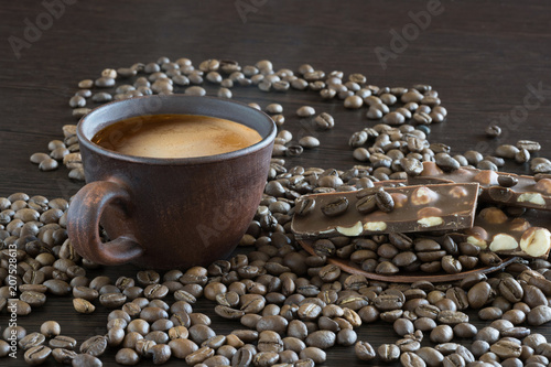 Foto op Aluminium Cafe Cup of coffee, chocolate and fried coffee grains on a wooden background.