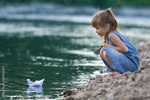 Adorable little cute blond girl in blue dress on riverbank pebbles playing with white paper origami boat on blue sparkling bokeh water background Canvas Print