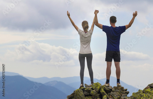 Fotografía  Back view of young couple, athletic boy and slim girl standing with raised arms on rocky mountain top enjoying breathtaking summer mountain view