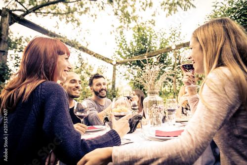 Leinwand Poster Friends having dinner in garden