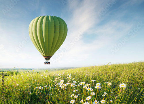 Air ballon above field with flowers at the summer time. Concept and idea of adventure