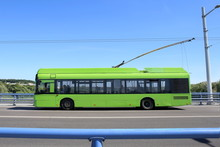 Trolley Bus Crossing Bridge. Green Trolleybus Moving On Road Against Blue Barrier Or Guard Rail.