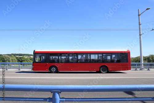 City bus crossing bridge. Red bus moving on road against blue barrier or guard rail.